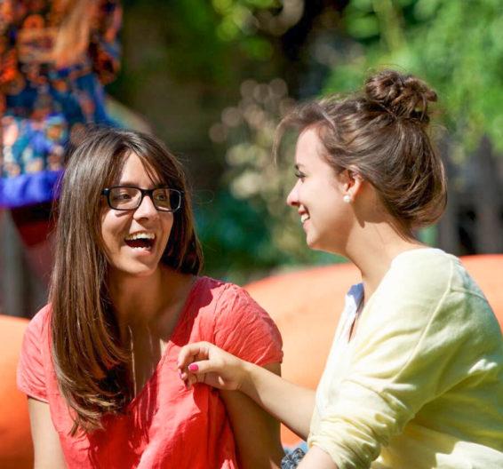 Две ученицы смеются на прогулке в солнечный день