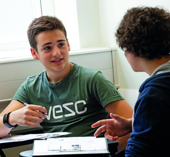 Deux Juniors conversant sur leurs cahiers de classe
