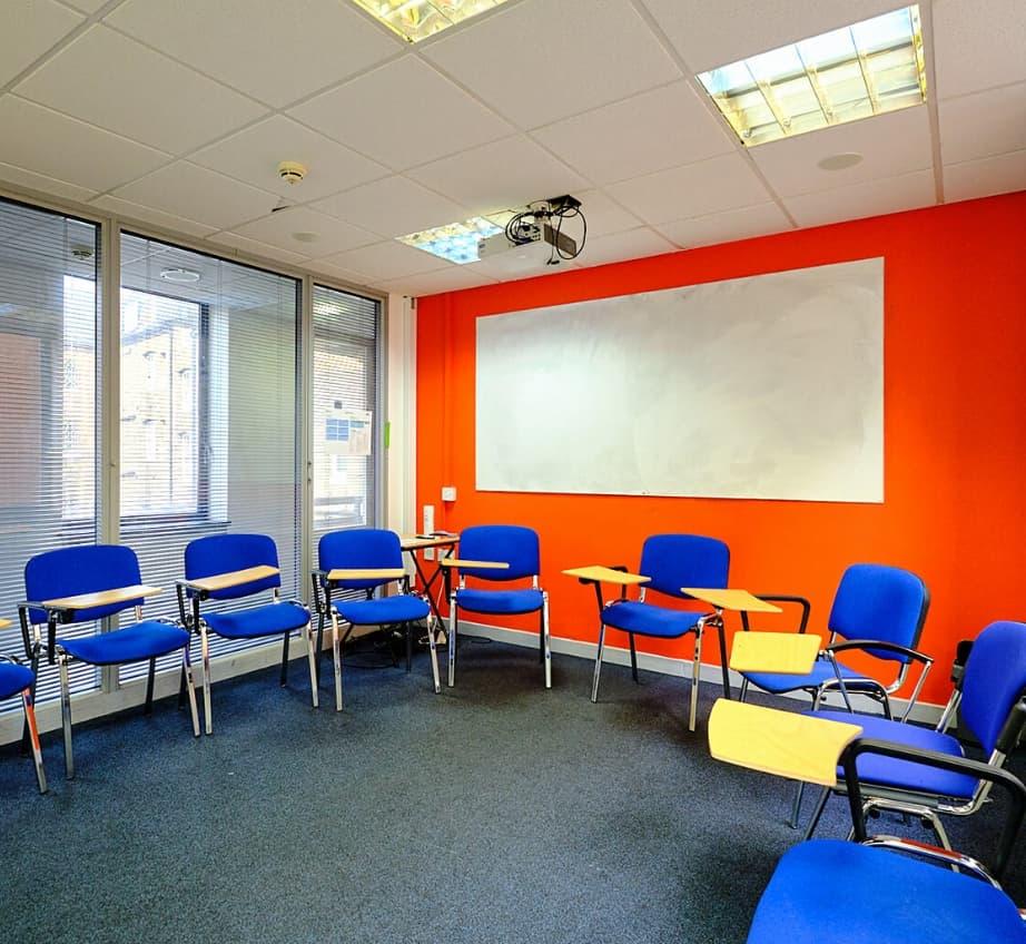 Une salle de classe vide au BSC Oxford avec des chaises et un tableau en arrière-plan