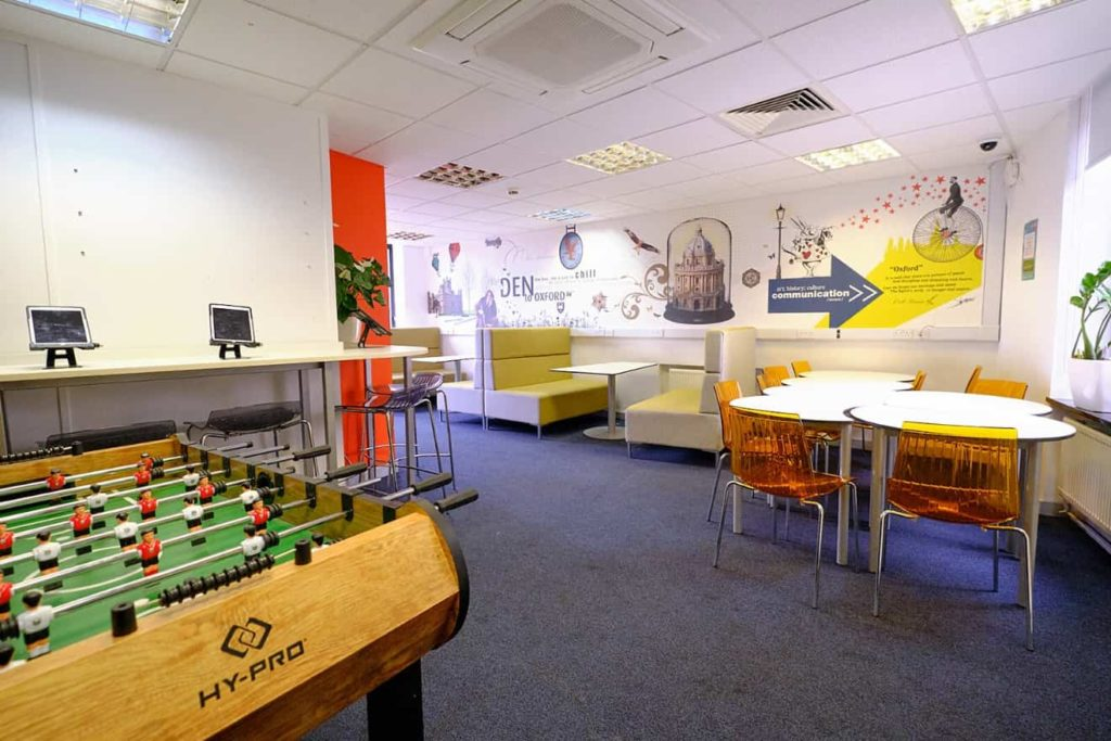 Salon des étudiants coloré au BSC Oxford avec canapés, babyfoot, plantes, tables et chaises