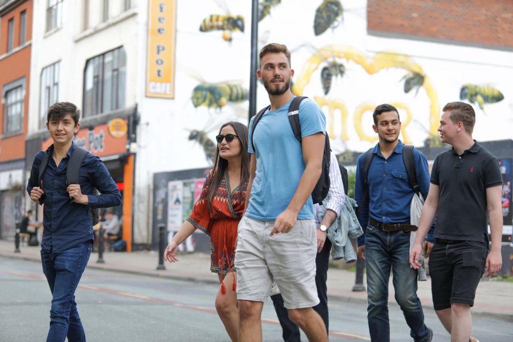 Groupe d'étudiants passant devant une fresque murale à Manchester