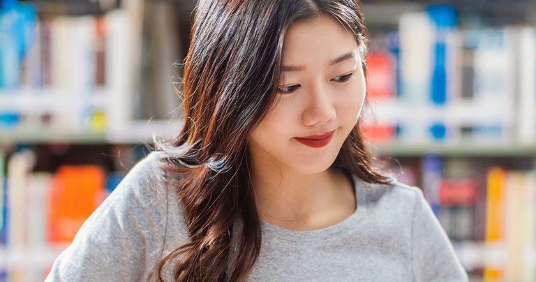 Jeune femme étudiant à la bibliothèque universitaire