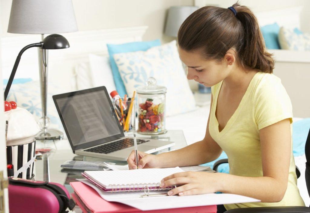 Étudiante en plein travail dans sa chambre chez l'habitant