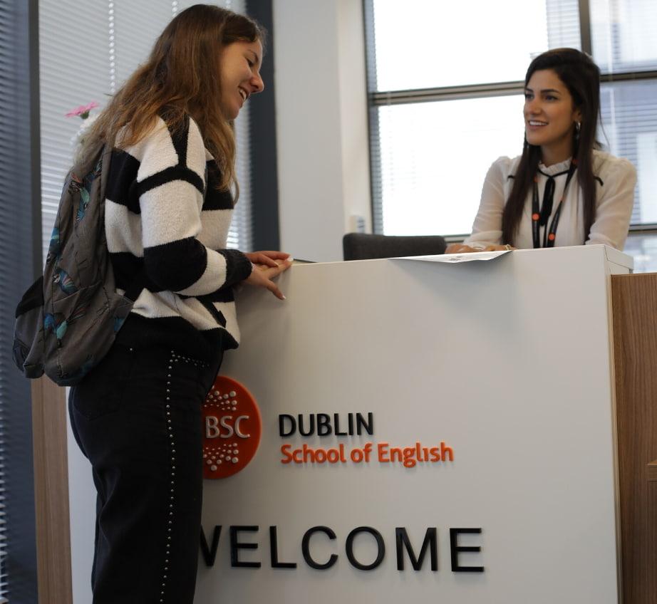 El mostrador de recepción de BSC Dublín con una empleada sonriente hablando con una estudiante