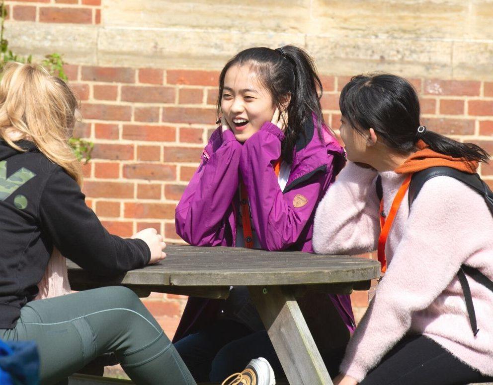 tres estudiantes sonrientes en un banco en el exterior de New Hall School
