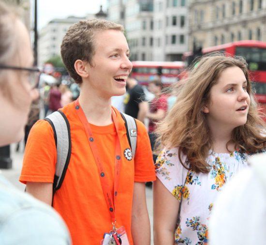 Dos jóvenes estudiantes visitan Londres emocionados. Hay un autobús rojo y edificios antiguos a su espalda.