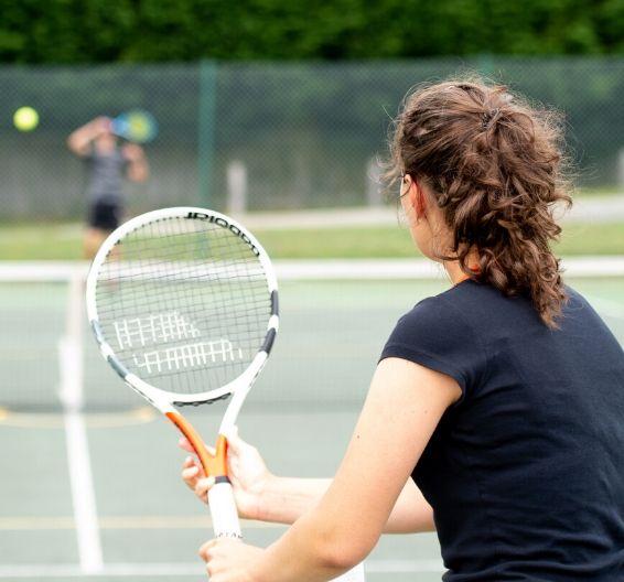 Alumna jugando a tenis en la escuela de verano
