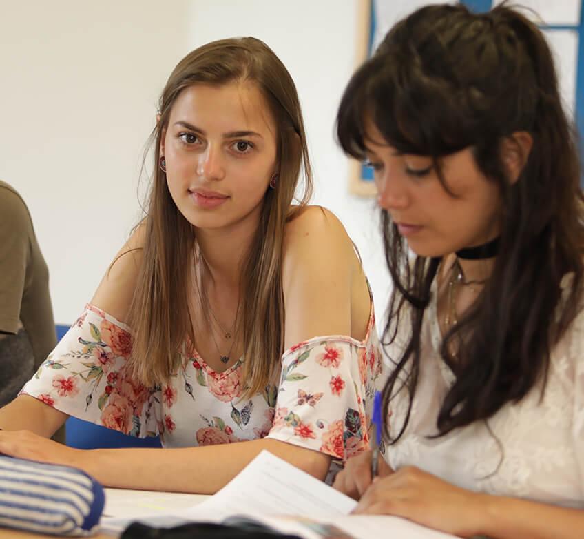 Estudiantes en una clase de idiomas, una mirando a la cámara