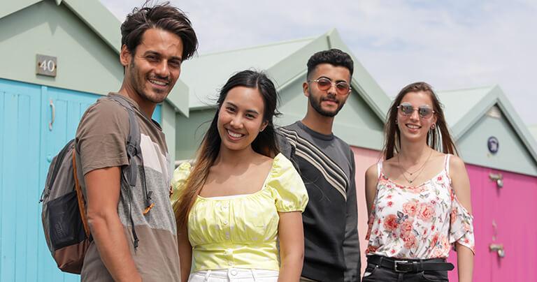 Cuatro estudiantes veinteañeros en el paseo marítimo de Brighton junto a algunas coloridas casetas de playa