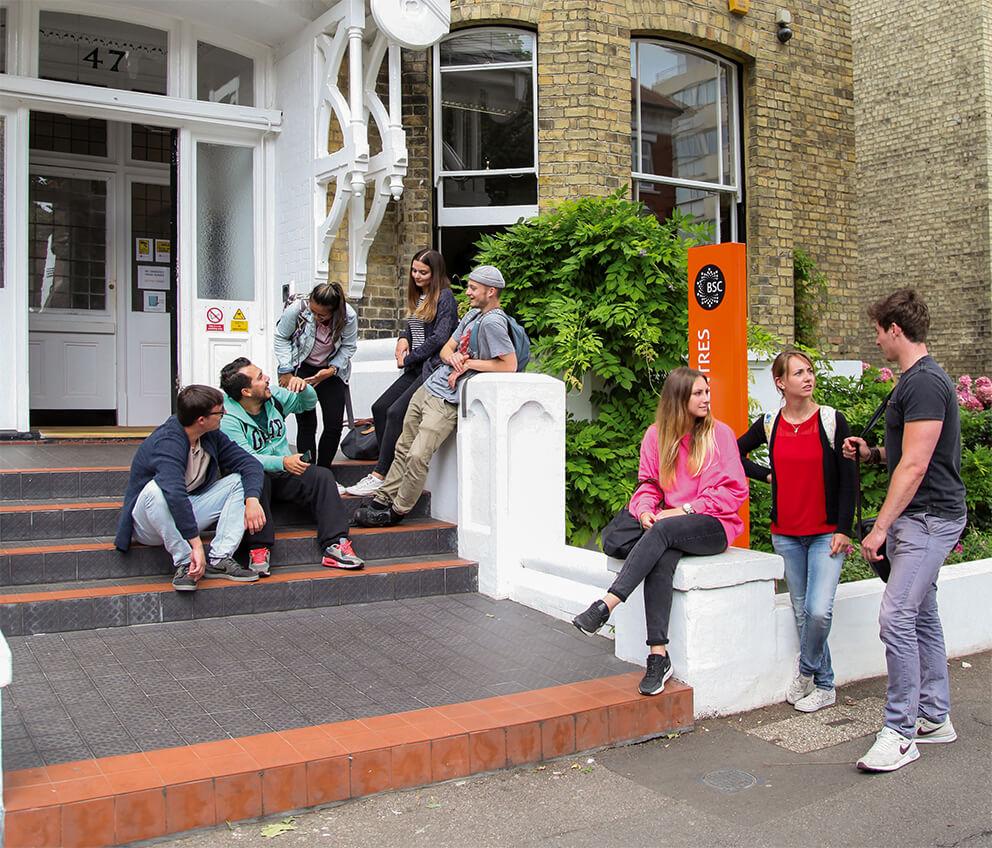 Estudiantes hablando en las escaleras exteriores de BSC Brighton