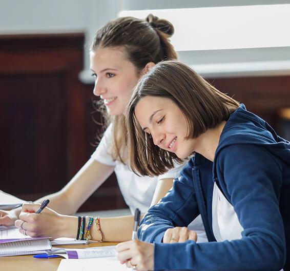 Dos estudiantes escribiendo en clase