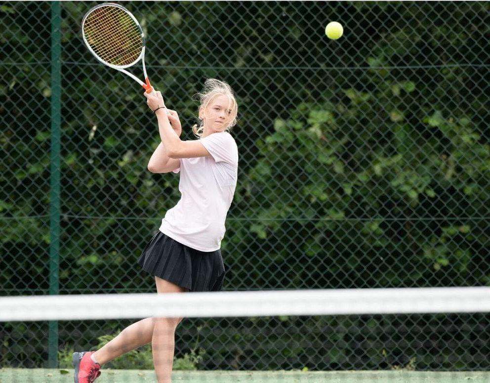 Una joven estudiantes con una raqueta de tenis se centra en golpear una pelota de tenis que va hacia ella