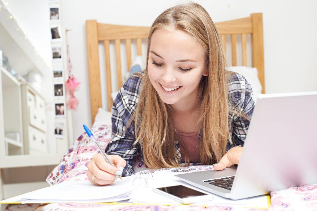 Chica rubia estudiando en la cama